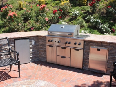 Elite outdoor grill setup with stone features and refrigerated storage
