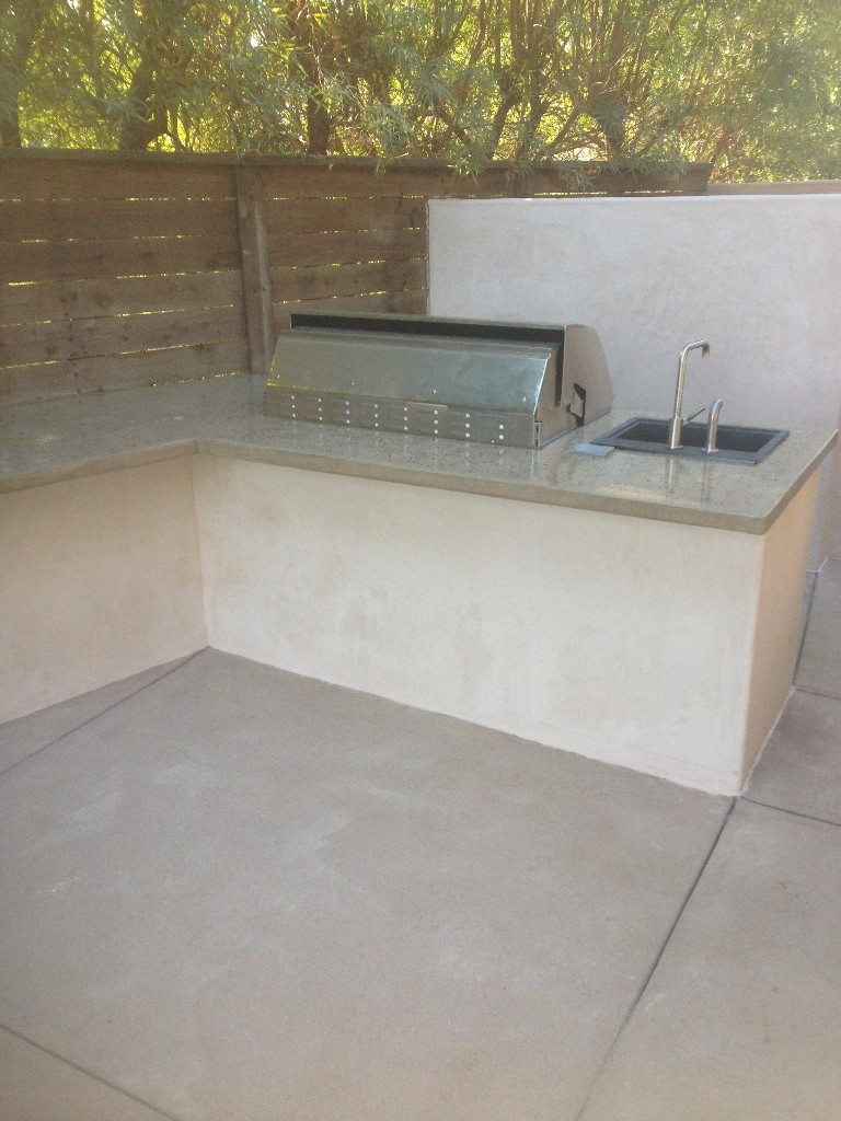 Backyard BBQ setup with concrete countertops and custom sink