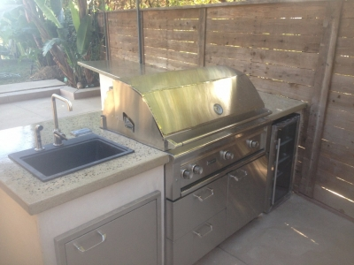 Backyard BBQ setup with concrete countertops and custom sink and fridge storage