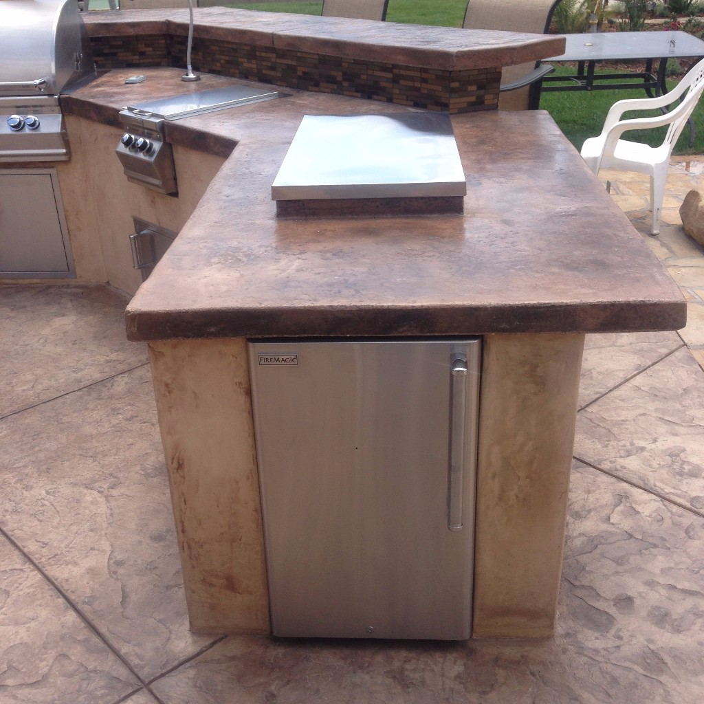 Custom BBQ Grill with concrete countertops and side accessories.