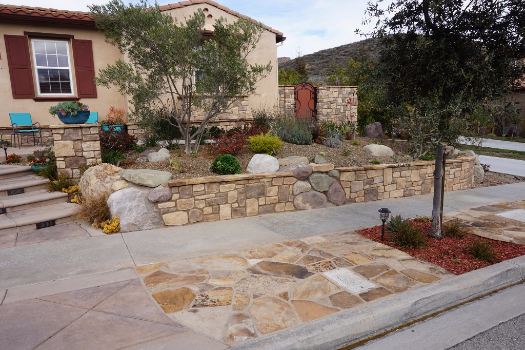 Sidewalk Features with stamped concrete and stone, plus stone retaining wall.