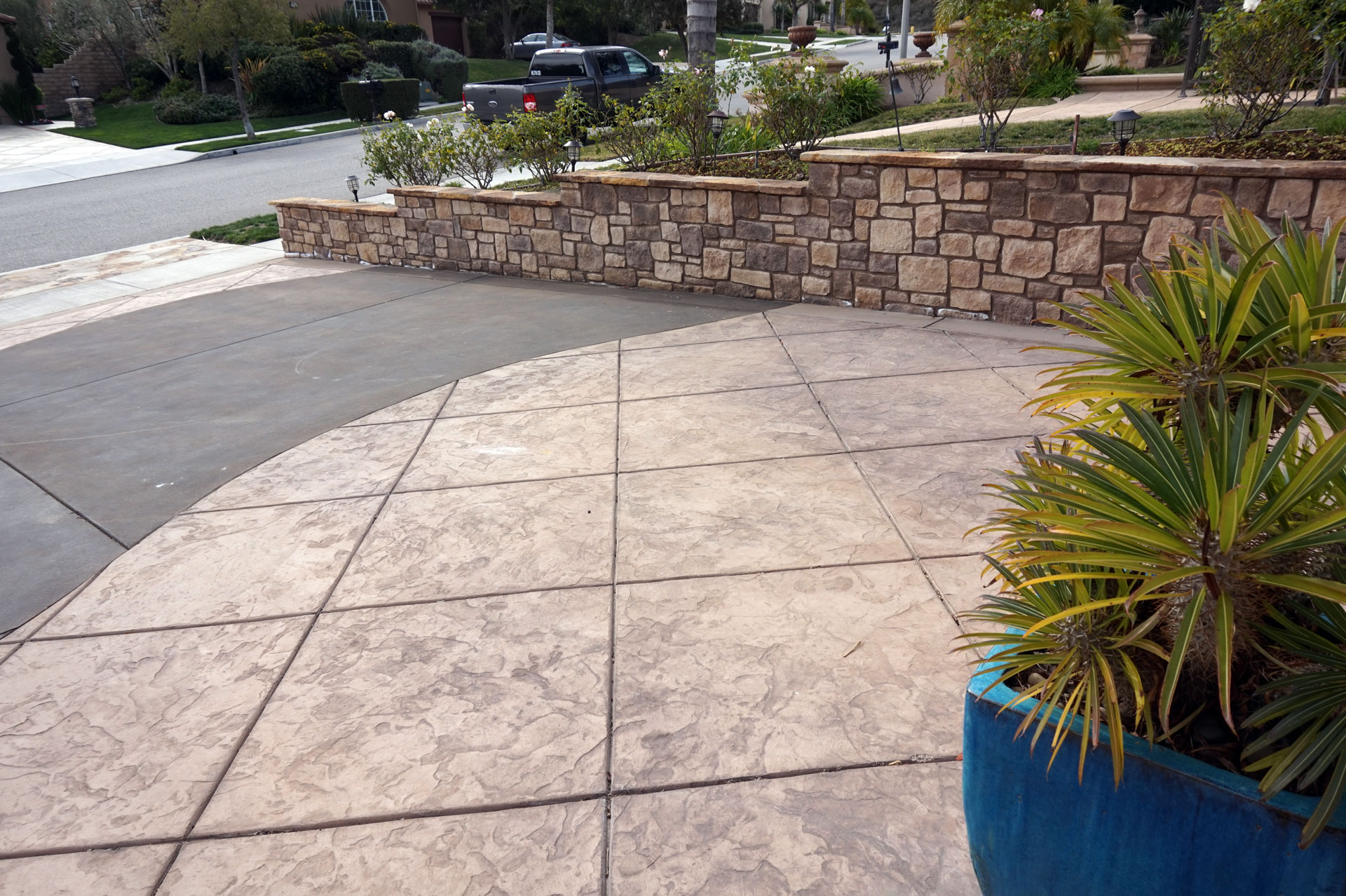 Stone Property Line Wall and Stamped Concrete Driveway